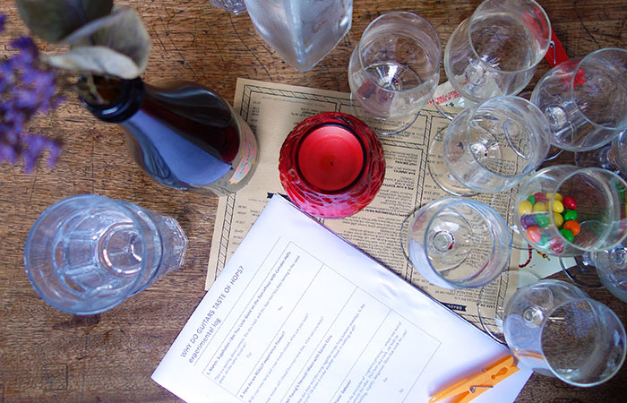 Glasses, bottles, and worksheets on a table, photographed from above