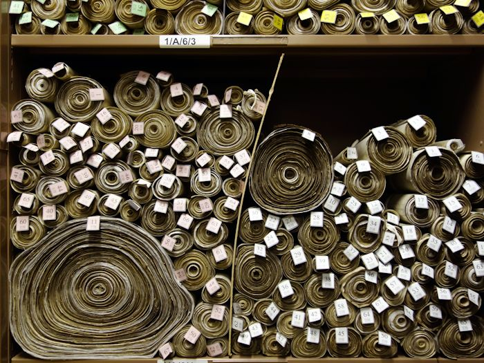Shelves containing stacked scrolls of parchment featuring British laws
