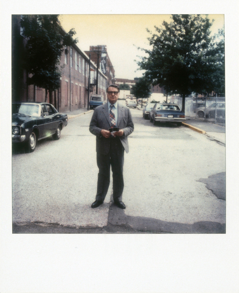 A Polaroid photo of Edwin Land standing in the middle of the street