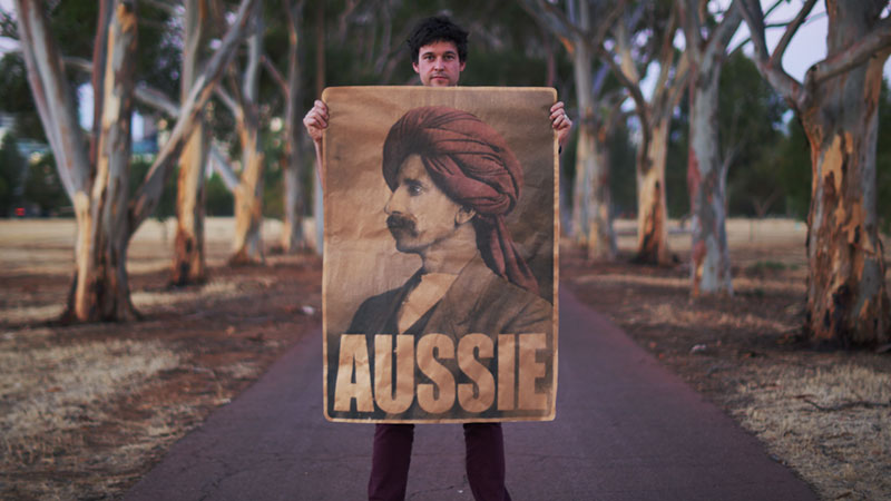 Peter Drew standing on a path in a park holding the 'Aussie' poster