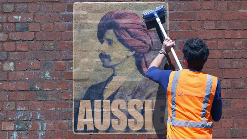 Peter Drew pasting an 'Aussie' poster on a brick wall