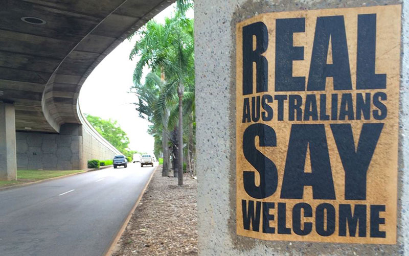 A 'Real Aussies Say Welcome' poster pasted on a bridge pylon